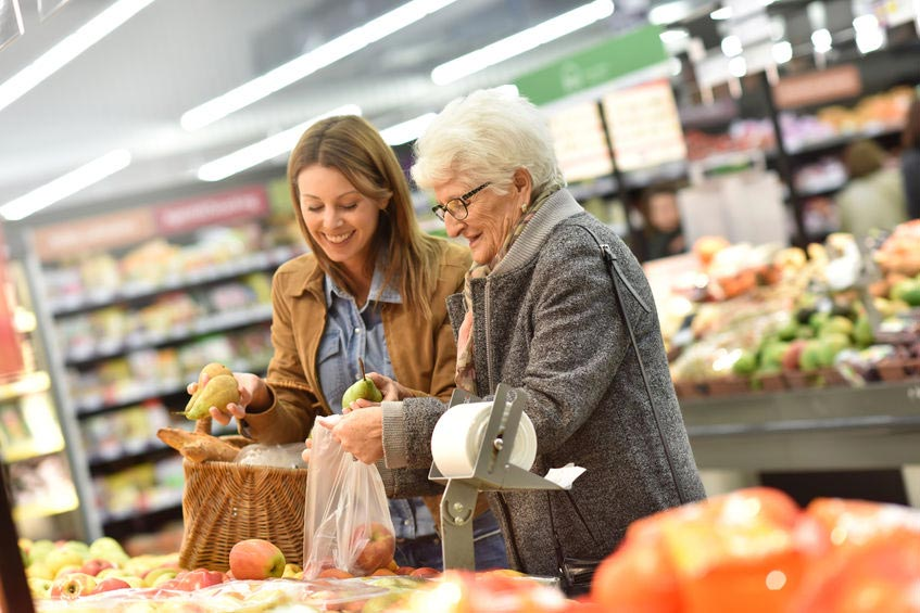 Volunteer helping elderly lady with her shopping